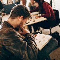 Adam çizim bakarak bir kafede